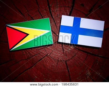 Guyana Flag With Finnish Flag On A Tree Stump Isolated