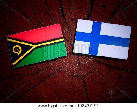 Vanuatu Flag With Finnish Flag On A Tree Stump Isolated