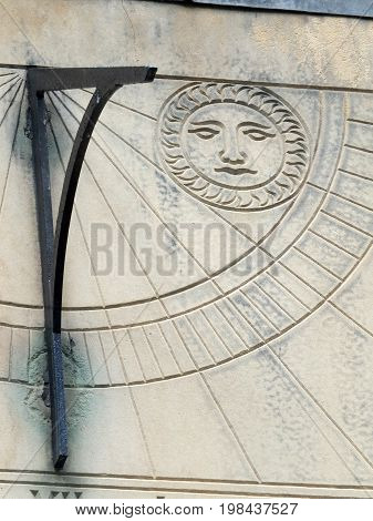 old sundial in close up with roman numeral and a carved symbol of the sun
