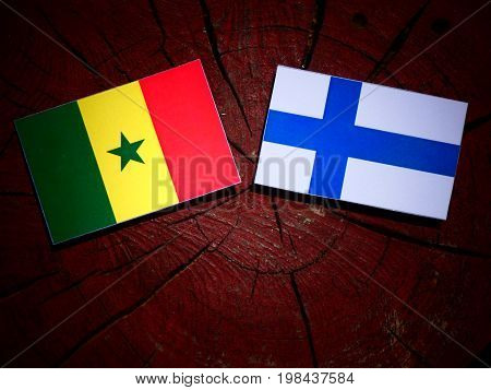 Senegal Flag With Finnish Flag On A Tree Stump Isolated