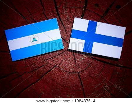 Nicaraguan Flag With Finnish Flag On A Tree Stump Isolated