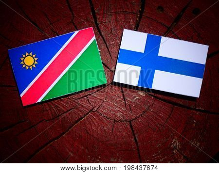 Namibian Flag With Finnish Flag On A Tree Stump Isolated
