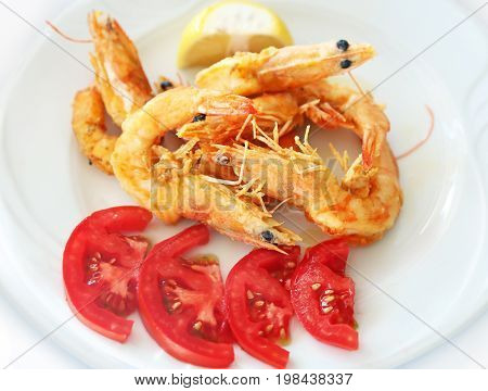 fried shrimps with fresh tomatoes at a greek tavern - delicious mediterranean seafood