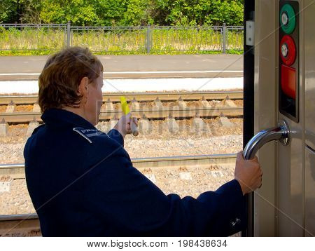 Moscow, Russia - August 05, 2010: Train departure. A woman conductor holds an alarm flag. View from the car