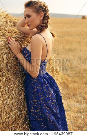 Girl With Blond Hair In Elegant Dress Posing On The Hay