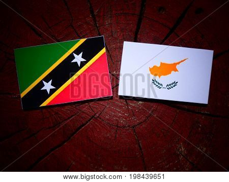 Saint Kitts And Nevis Flag With Cypriot Flag On A Tree Stump Isolated