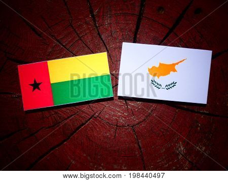 Guinea Bissau Flag With Cypriot Flag On A Tree Stump Isolated