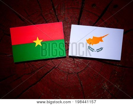 Burkina Faso Flag With Cypriot Flag On A Tree Stump Isolated