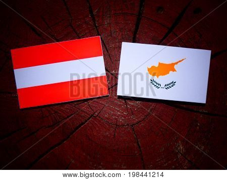 Austrian Flag With Cypriot Flag On A Tree Stump Isolated
