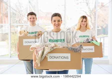 Volunteers with boxes indoors. Poverty concept