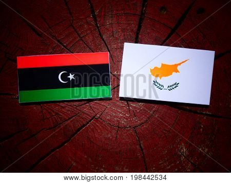 Libyan Flag With Cypriot Flag On A Tree Stump Isolated