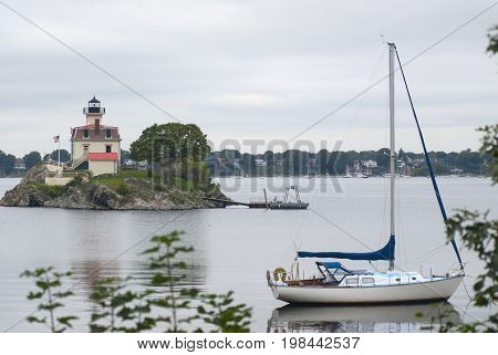 Sailboat anchored by Pomham Rocks lighthouse on a cloudy day in Rhode Island.