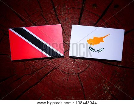 Trinidad And Tobago Flag With Cypriot Flag On A Tree Stump Isolated