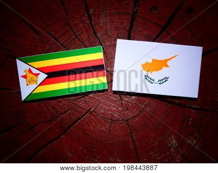 Zimbabwe Flag With Cypriot Flag On A Tree Stump Isolated