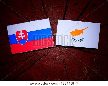 Slovakian Flag With Cypriot Flag On A Tree Stump Isolated