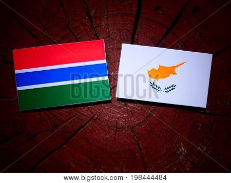 Gambian Flag With Cypriot Flag On A Tree Stump Isolated