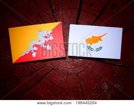 Bhutan Flag With Cypriot Flag On A Tree Stump Isolated