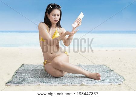 Beautiful woman using sunblock while sitting on the mat and sunbathing on the beach