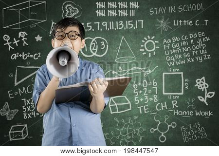 Boy student speaking on megaphone while holding a book with chalkboard background in classroom