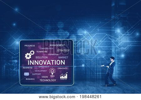 Young businesswoman is pulling innovation text on the billboard while standing in the cyberspace