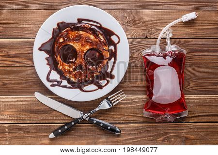 Slapjack in form of skull on wooden table with packet of blood
