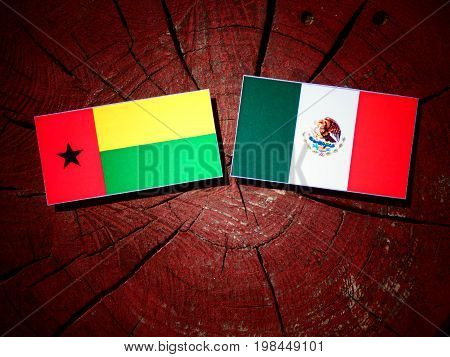 Guinea Bissau Flag With Mexican Flag On A Tree Stump Isolated