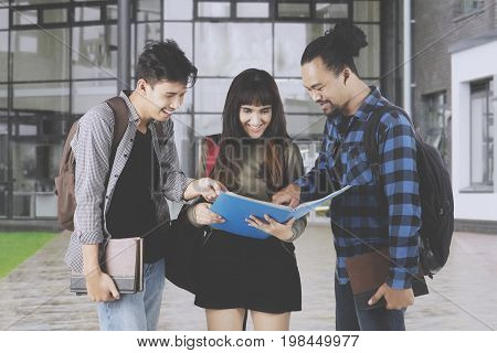 Three multiracial college students are discussing an assignment while standing near the university building
