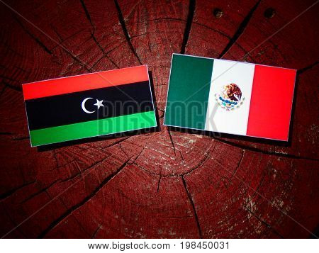 Libyan Flag With Mexican Flag On A Tree Stump Isolated