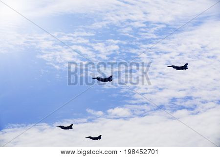 Photo of four jet army planes flying in the blue sky while doing maneuvers