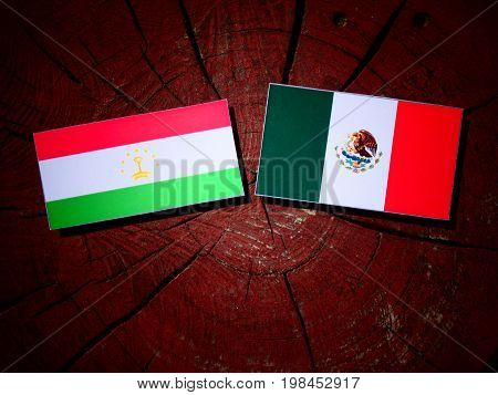 Tajikistan Flag With Mexican Flag On A Tree Stump Isolated