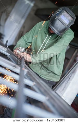 Electric wheel grinding on steel structure in factory. Sparks from the grinding wheel. Protective mask poster