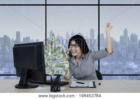 Young businesswoman looks happy talking on the cellphone while looking at dollar money on the monitor from internet