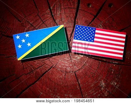 Solomon Islands Flag With Usa Flag On A Tree Stump Isolated