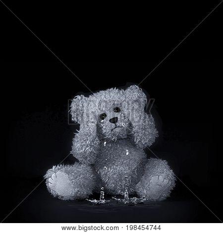 A fuzzy teddy bear crying with tears splashing on a black background.