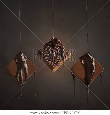 Three squares of chocolate fudge with chocolate syrup dripping onto them.