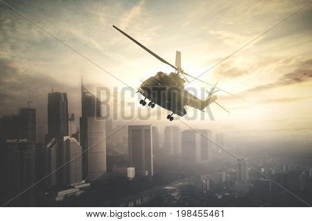 Image of military helicopter is flying over downtown while doing patrols shot at sunrise time