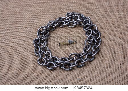 Figurine Trapped In The Circle Of A Chain
