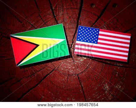 Guyana Flag With Usa Flag On A Tree Stump Isolated