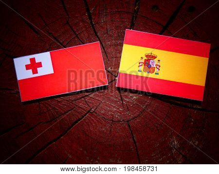 Tongan Flag With Spanish Flag On A Tree Stump Isolated