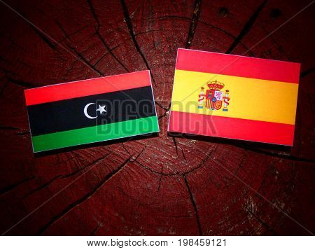 Libyan Flag With Spanish Flag On A Tree Stump Isolated