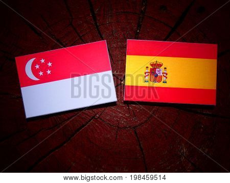 Singaporean Flag With Spanish Flag On A Tree Stump Isolated