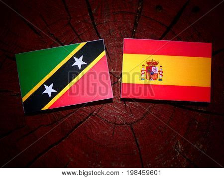 Saint Kitts And Nevis Flag With Spanish Flag On A Tree Stump Isolated
