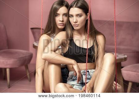 Fashion Photo Of Attractive Caucasian Twins Sisters Posing In Pink Interior.