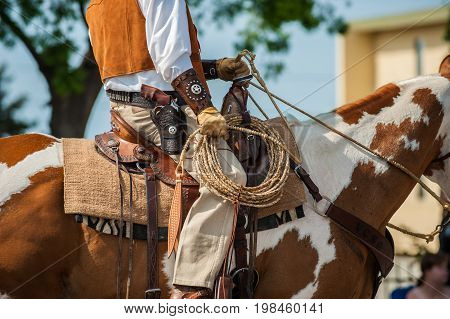 Mounted sheriff on Pinto holding lasso in hand and gun in holster. poster