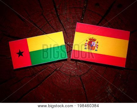Guinea Bissau Flag With Spanish Flag On A Tree Stump Isolated