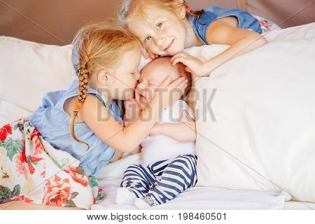 Lifestyle portrait of cute white Caucasian girls sisters holding kissing little baby sitting on bed. Older siblings with younger brother sister newborn. Family love bonding together concept.