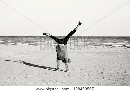 Black and white portrait of funny white Caucasian child kid teenager doing cartwheel playing on beach on sunset. Happy lifestyle childhood concept