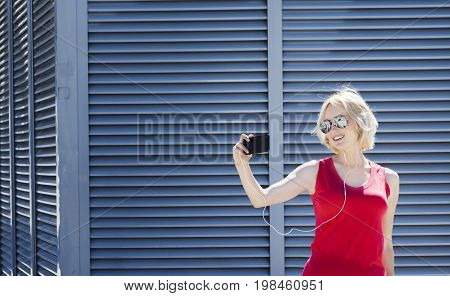 Female dressed in red t-shirt and sun-glasses listening to musiс in headphones and taking a shot on cellphone