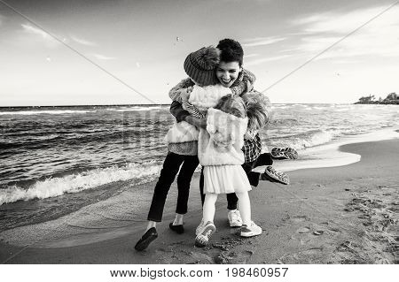 Group black-and-white portrait of Caucasian family mother with three children kids hugging smiling laughing on ocean sea beach on sunset outdoors. Happy lifestyle childhood concept