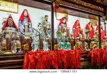 Shanghai, China - Nov 6, 2016: Inside the 600-year-old Old City God Temple. Rare figurines of Taoist deities displayed in glass cabinet. Some reflections can be seen. Low-light image.